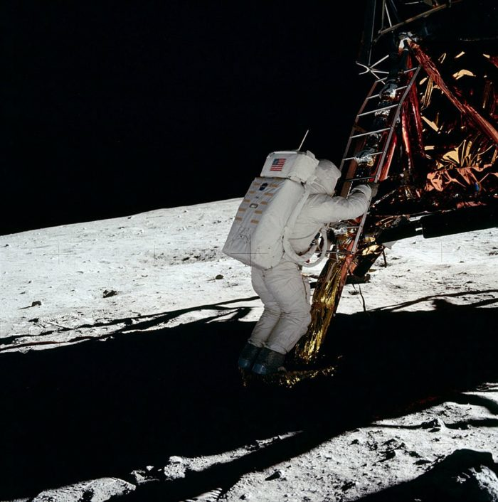 An astronaut climbing down from the Lander to the Moon's surface