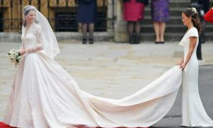 Image of Kate Middleton's wedding dress with the trail being held by one of the bridesmaids