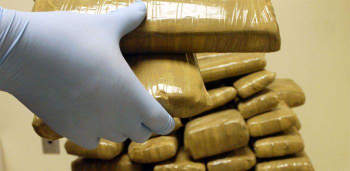 A hand examining a stash of smuggles heroin