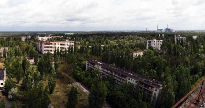 The town of Pripyat with Chernobyl power plant in the distance