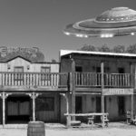 Wild West buildings with UFO flying over.