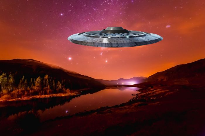 A depiction of a UFO over the countryside