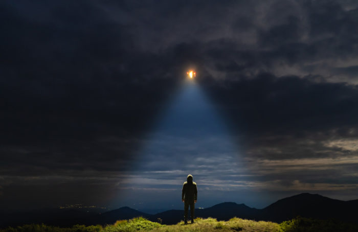 Depiction of a UFO over a person