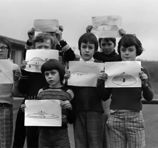 Broad Haven pupils display their drawings of the UFO.
