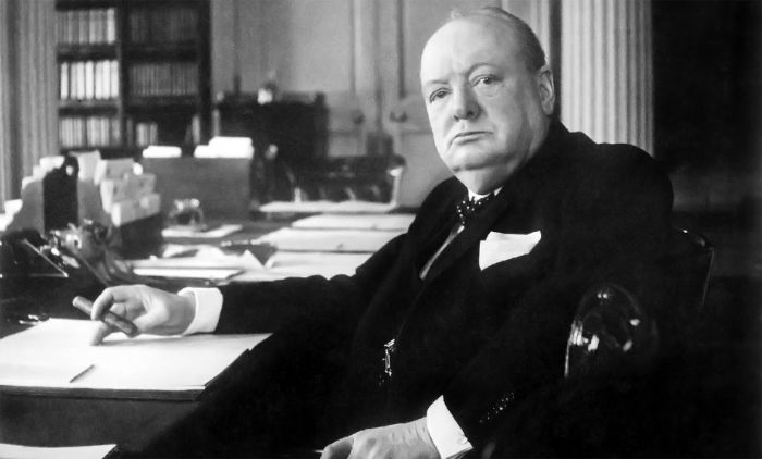 Churchill in his office with cigar while writing.