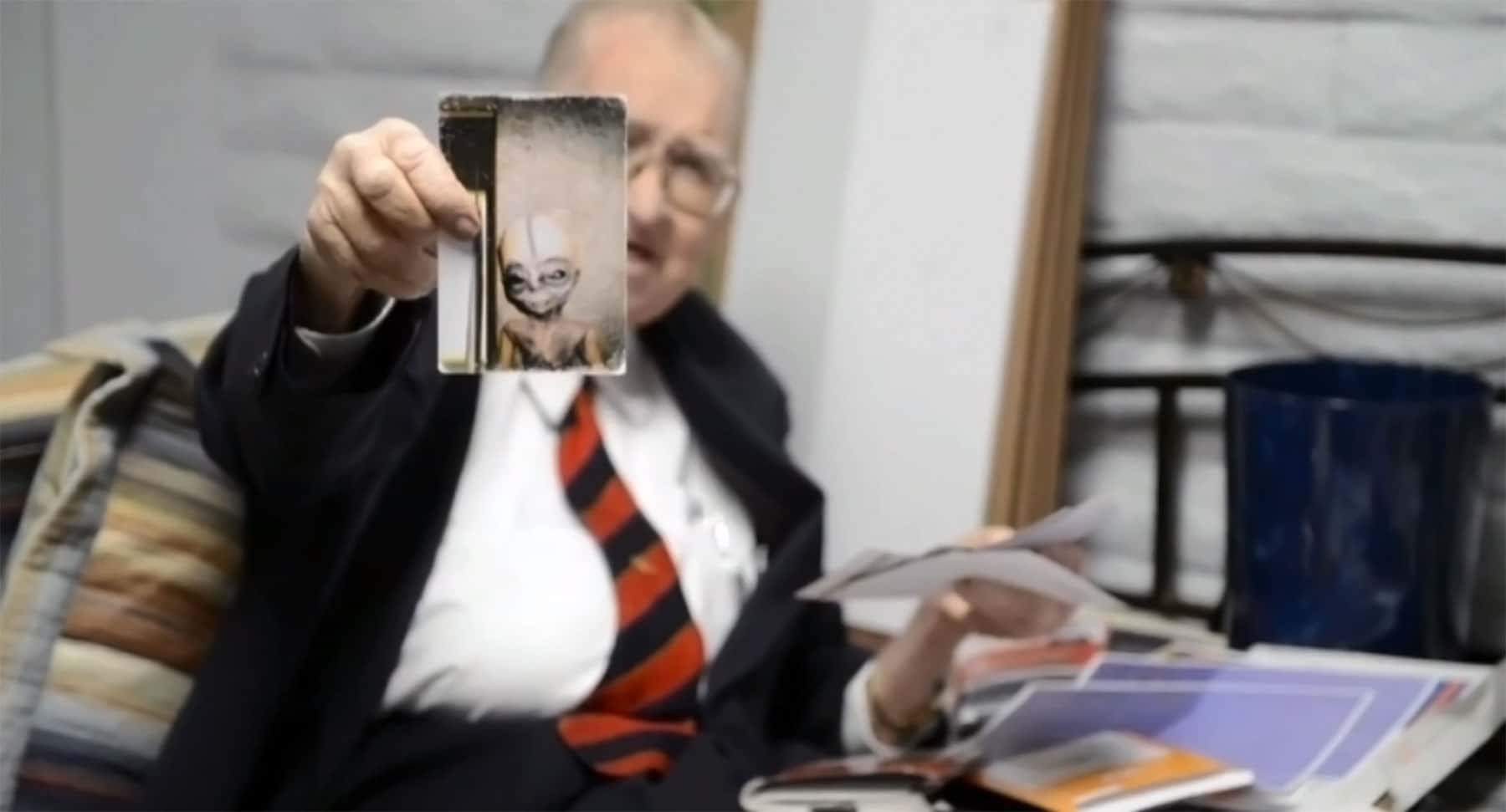 Boyd Bushman holding a photo of an alien life form.