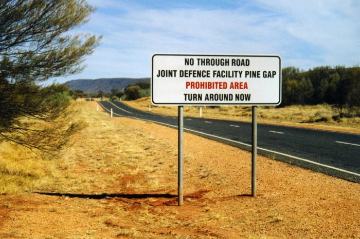 Warning sign outside Pine Gap on a lonely road
