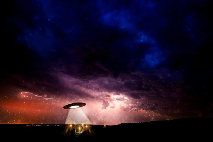 A depiction of a UFO shining a light into a field