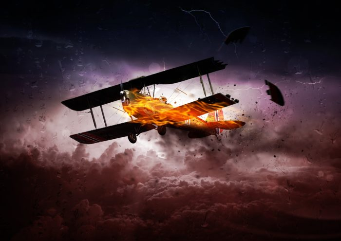 A picture of a plane on fire in a cloudy sky