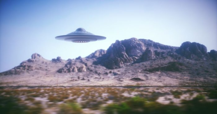A depiction of a UFO over a mountainous terrain