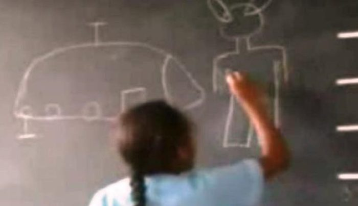 One of the children draws an example of the alien figures on the blackboard