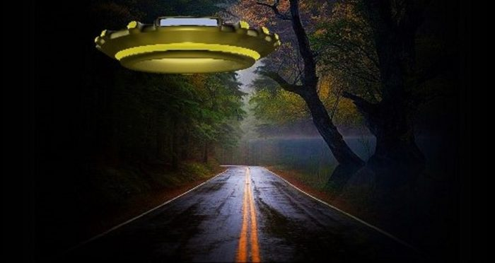 A depiction of a UFO hovering over a quiet road