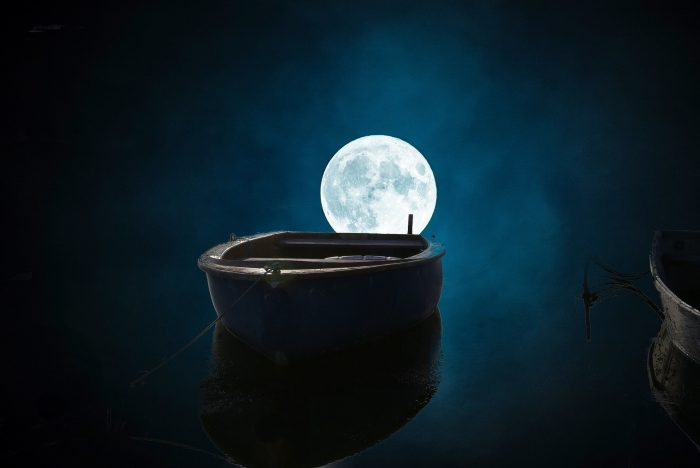 A lone fishing boat on the water under a full moon