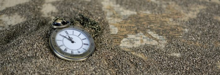 A clock face dropped in the sand