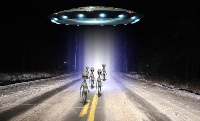 A depiction of a UFO with aliens emerging from it