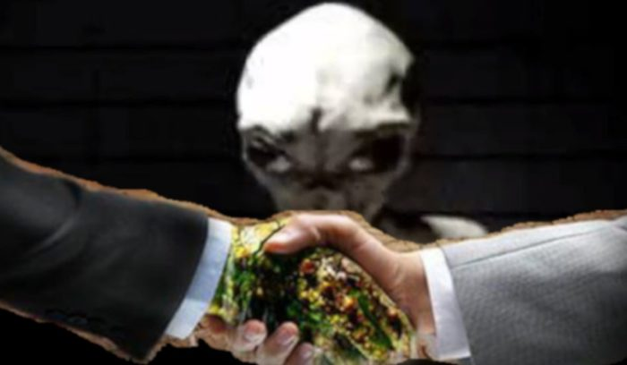 a handshake between a man and an alien with an alien in the background