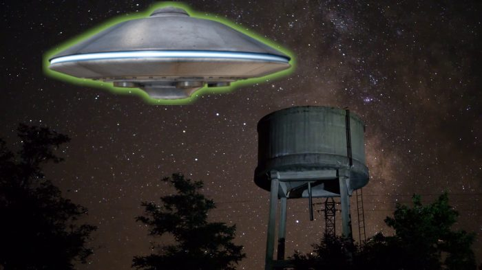 A depiction of a UFO hovering over a water tower
