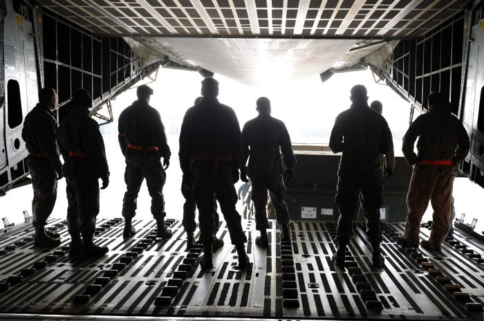 A picture of several men unloading cargo from the inside of the back of a plane