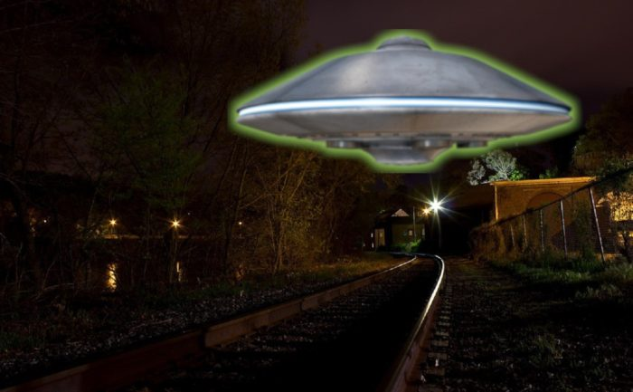A depiction of a UFO hovering over a rail track