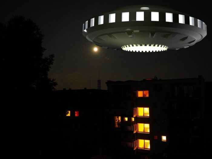 A depiction of a UFO hovering over apartments