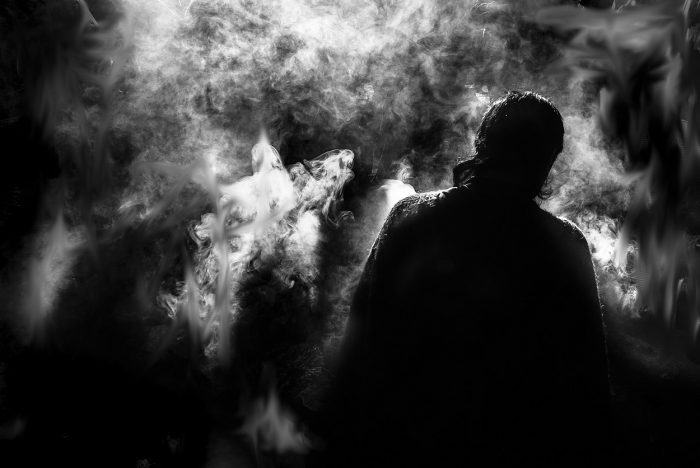 The dark image of man facing away looking into a strange smoky fog
