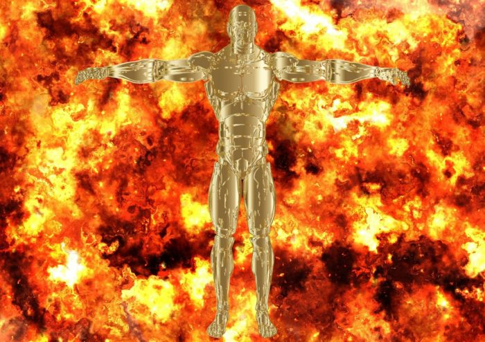 A gold robotic figure standing with a backdrop of flames