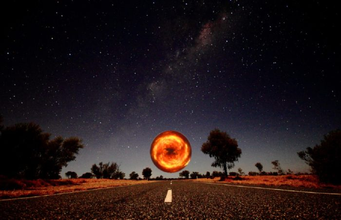 A depiction of a lonely highway with a glowing orb hovering