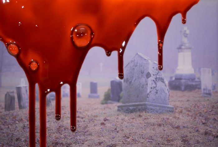 A picture of a graveyard with superimposed blood dripping down the screen