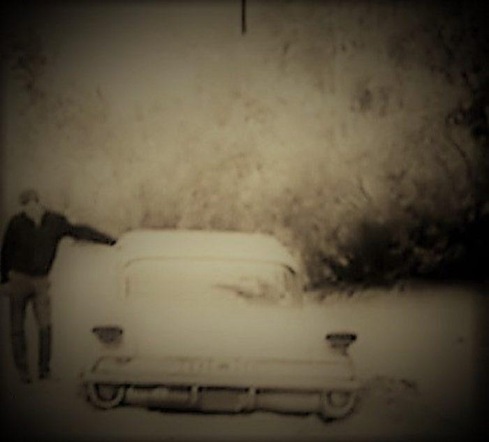 Douglas Tibbets examines his car