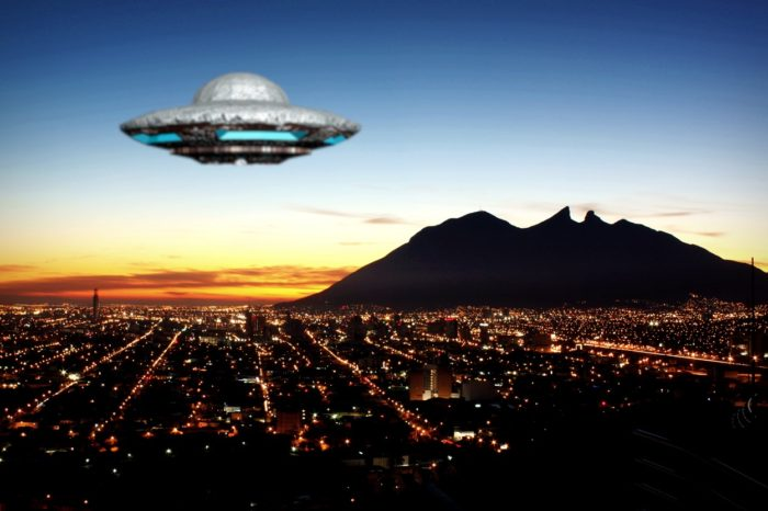 Superimposed UFO over a night city setting