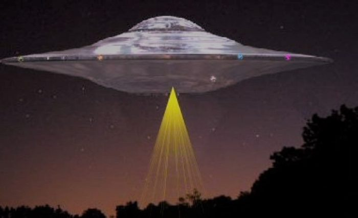 A depiction of a UFO hover over woodland at night