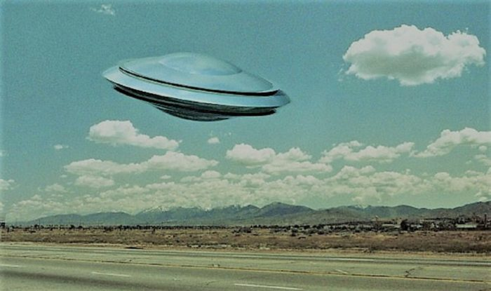 A depiction of a UFO over a lonely road