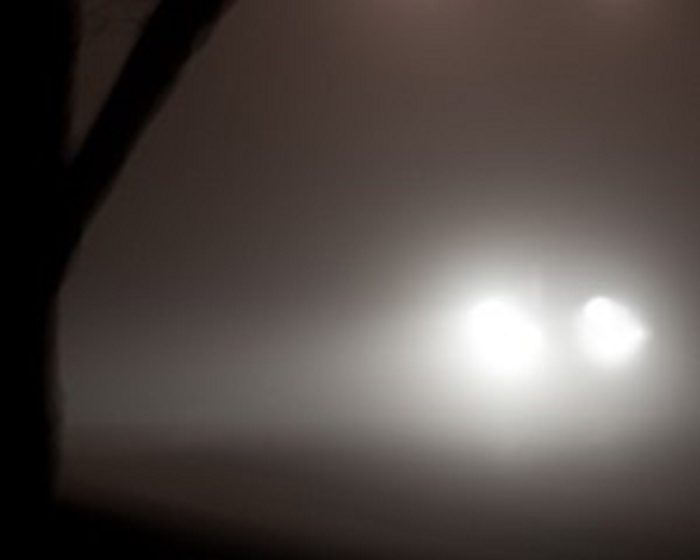 A pair of headlights emerging from the fog