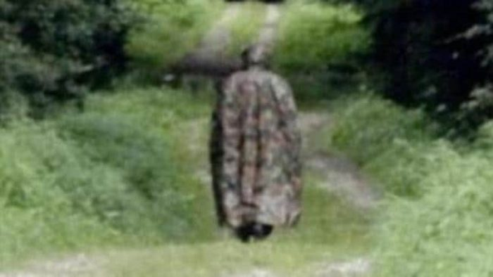 A picture of a cloaked man walking away from the camera on a country path