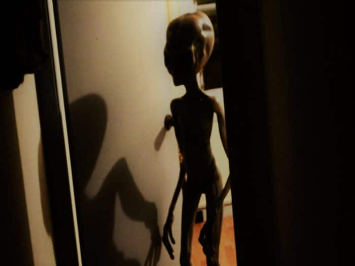 A depiction of a grey alien entering a room