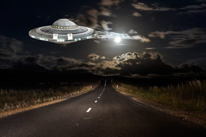 A superimposed UFO on a lonely highway