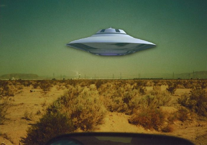 A depiction of a UFO hovering over a desert