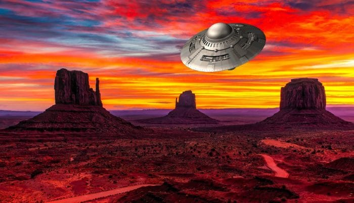 A depiction of a UFO over an Arizona desert at sunset