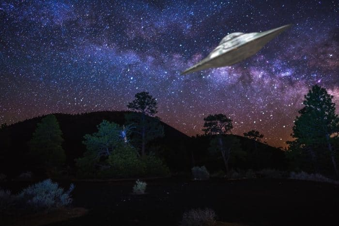 A depiction of a UFO flying over desert and woodland