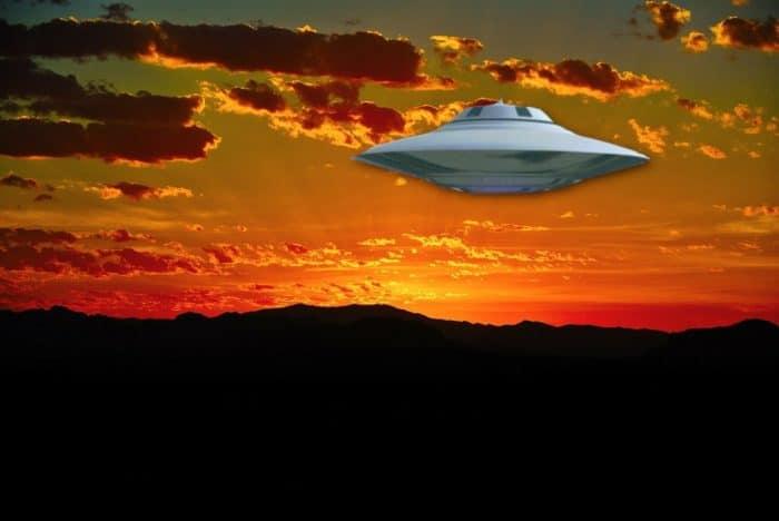 A silver UFO in a sunset sky