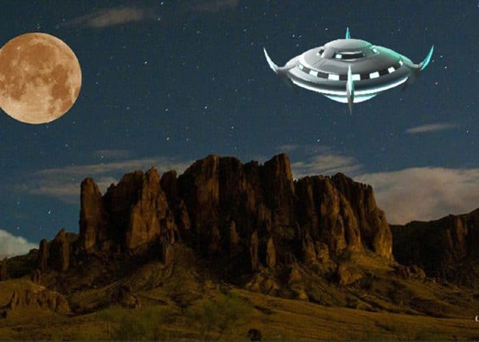 A depiction of a UFO hovering over desert at night