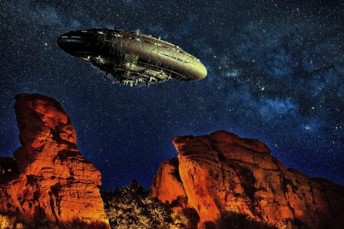 A superimposed UFO over a desert with a night sky