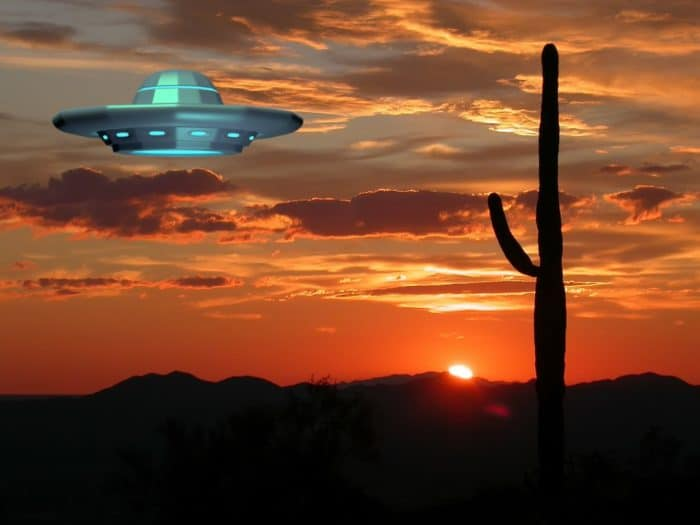 A superimposed UFO hovering over a desert at sunset