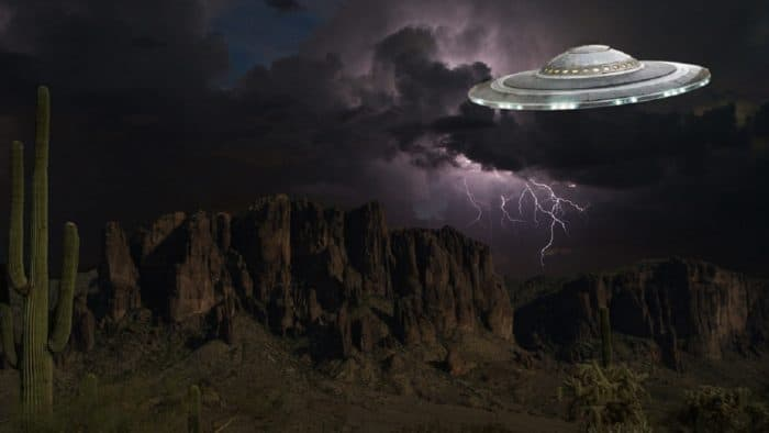 A depiction of a UFO over a desert landscape at night