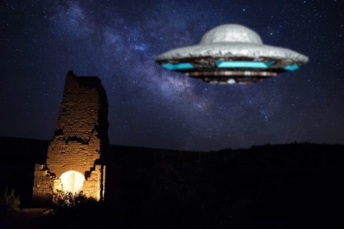 A depiction of a UFO hovering over a ruined building at night