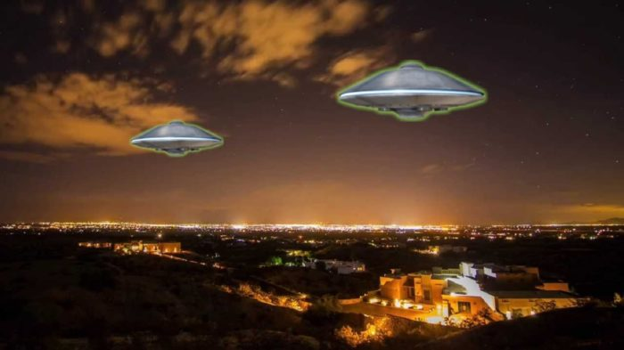 Two superimposed UFOs over a night scene viewed from the hills
