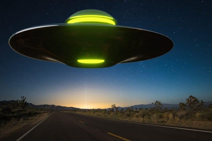 A depiction of a UFO hovering over a lonely road