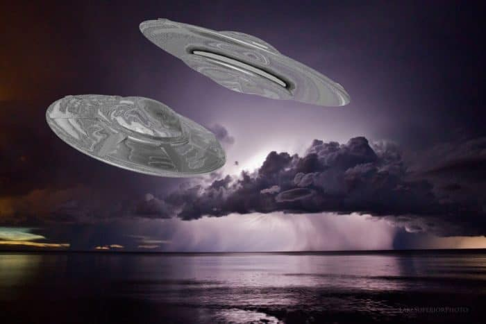 A depiction of UFOs flying over the water at night