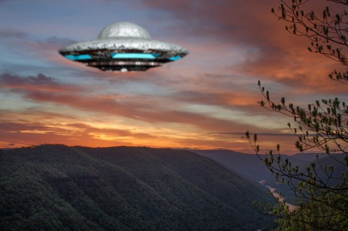 A depiction of a UFO hovering over mountains