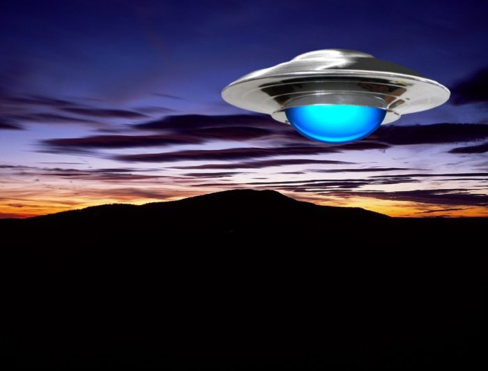 A superimposed UFO over a mountain at night